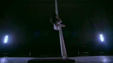 Woman dancer on white aerial silk, aerial contortion. Slow motion.