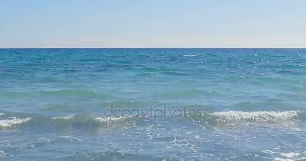 Vlny na pobřeží. Jasné modré vody