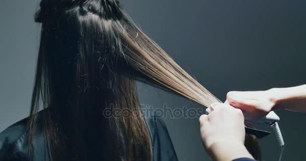 Ženy ruce, aby vlasy Uložte proceduru. Přístroj, který vlasy regenerace s červené neonové světlo