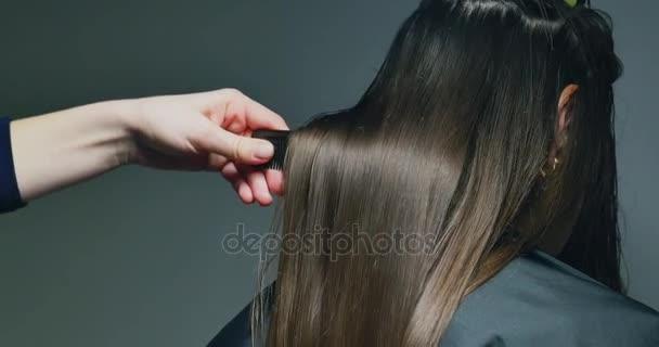 Žena stylista česání vlasů. Příprava vlasů
