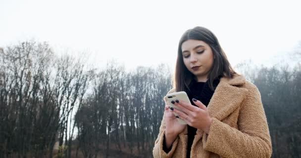 Porträt einer jungen attraktiven Frau, die auf dem grünen Rasen des Herbstparks am Wald lächelt und auf ihr Smartphone blickt