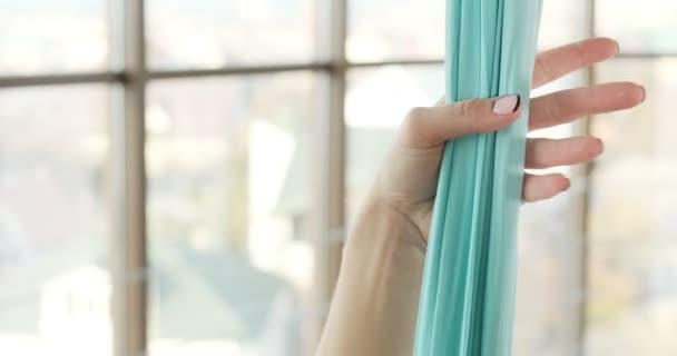 Gyönyörű fiatal nő repül jógázni a szobában, nagy ablakokkal. Vonzó nő, aki függőágyban dolgozik a testével. Pihenési koncepció