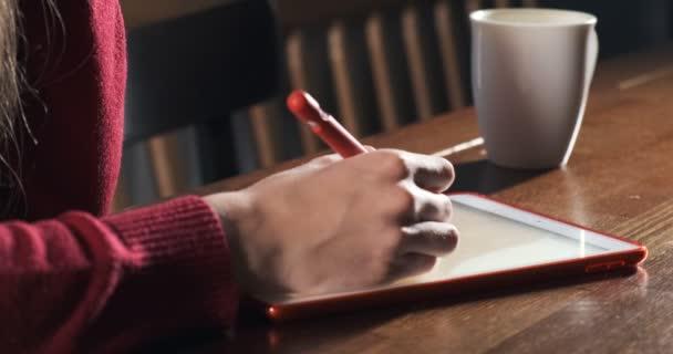 Zblízka žena návrhářka sedí a pracuje za stolem. Současná mladá žena kreslí a používá pero s digitálním tabletem. Atraktivní dívka vytváří digitální ilustrace