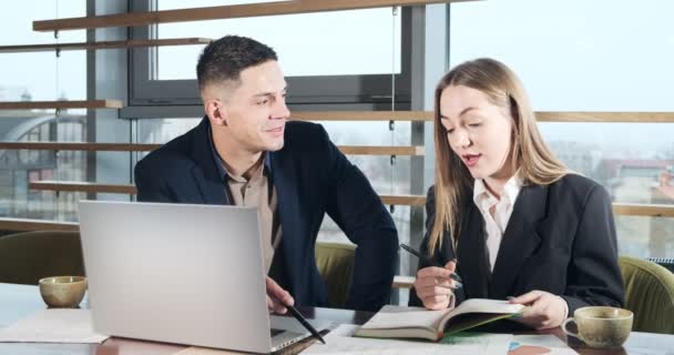 Muž a žena diskutují o práci v jasně osvětlené moderní kanceláři. Znepokojený muž a žena pracují s notebookem a mapuje papíry u stolu. Podnikatelé diskutují o novém konceptu spouštěcího projektu