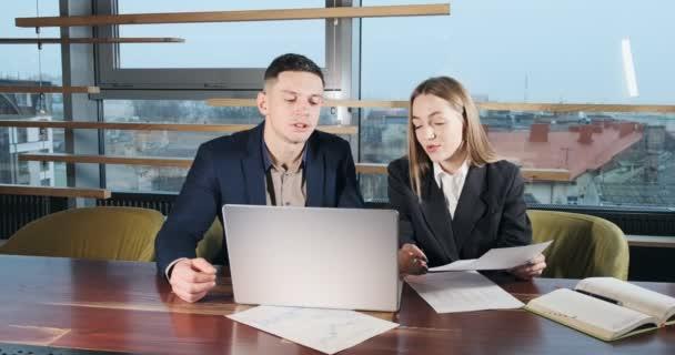 Muž a žena diskutují o práci v jasně osvětlené moderní kanceláři. Znepokojení muži a ženy, kteří pracují s notebookem a mapami. Podnikatelé diskutují o novém konceptu spouštěcího projektu. Pohybující se kamera