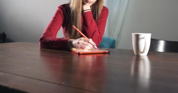 Talentovaná inovativní hezká návrhářka sedí a pracuje za stolem. Současná mladá žena píše, kreslí a používá pero s digitálním tabletem. Atraktivní dívka vytváří digitální ilustrace