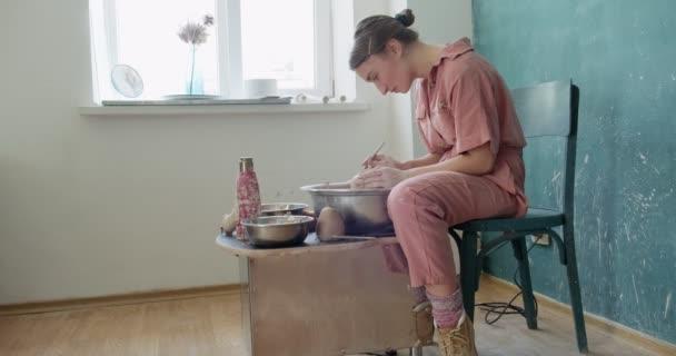 Töpferin sitzt und macht eine Tasse auf der Töpferscheibe. Frau, die Keramik herstellt. Töpfern, handwerkliches und kreatives Geschick