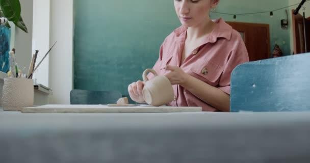 Töpferin sitzt am Tisch und macht eine Tasse. Frau, die Keramik herstellt. Töpfern, handwerkliches und kreatives Geschick