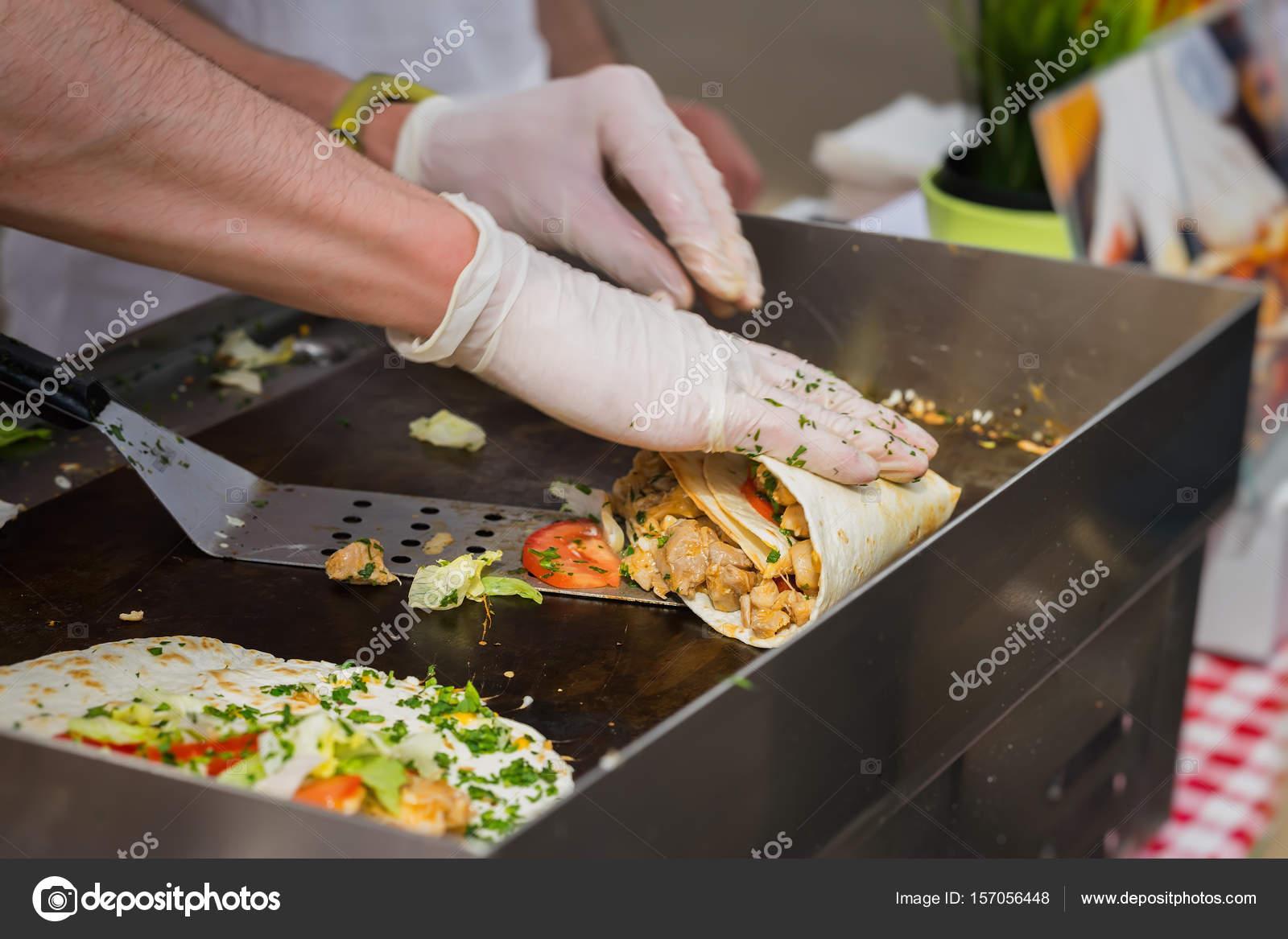 Nahaufnahme der Hände von Cook in Handschuhen Vorbereitung Fajitas ...