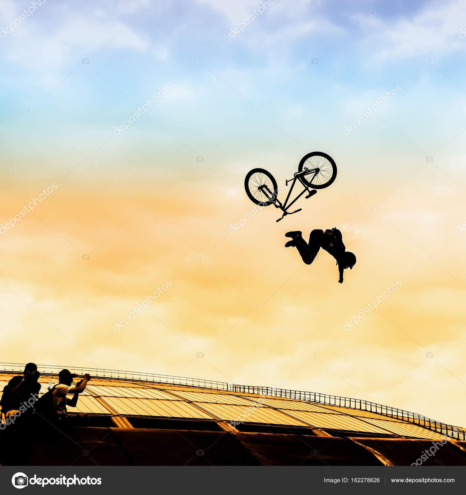Extrem Sport. Silueta de hombre joven haciendo salto con bicicleta ...