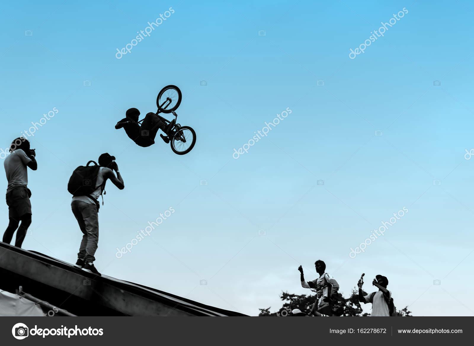 Ciclistas extremos, hombre joven haciendo salto con bicicleta bmx ...