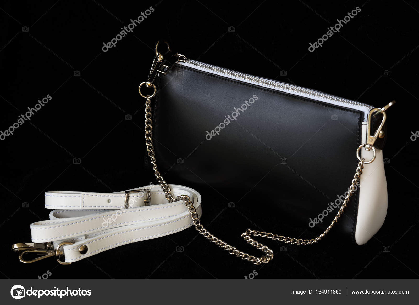 Close-up of leather handbag, always classic combination, black and white color with strap and chain, low key. For modern pattern, wallpaper or banner design ...