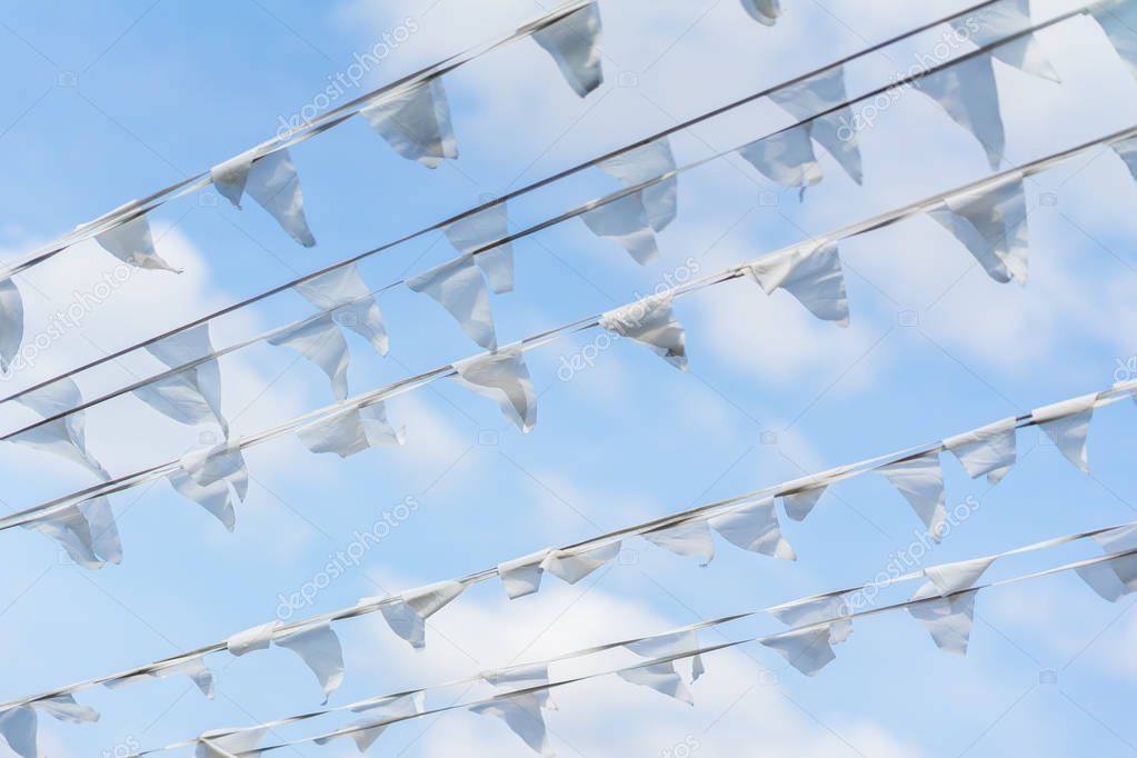 Garland of white flags of triangular shape, pennants in blue sky. City street holiday. Sea, marine theme. Modern background, banner design. Fest, celebration concept