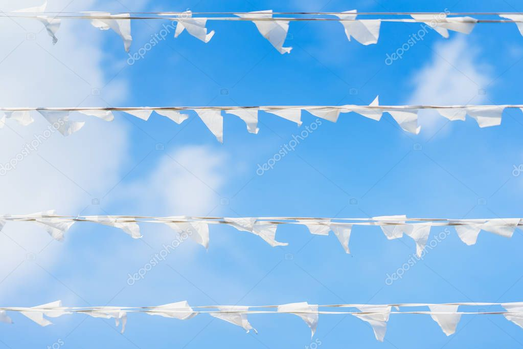 White flags of triangular shape, pennants against blue cloudy sky in horizontal garland. City street holiday, Festival, marine theme, celebration concept