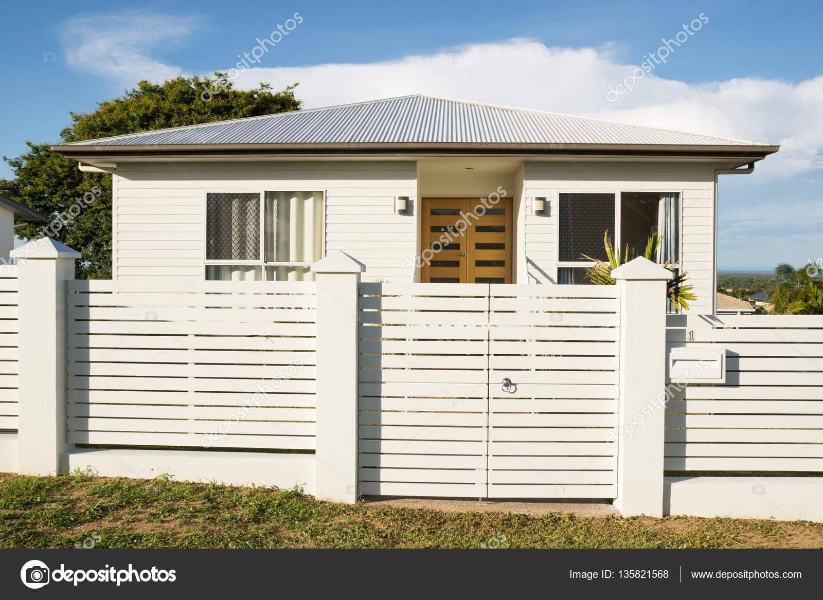 Nieuwe modern eigentijds huis buitenkant met omheining en
