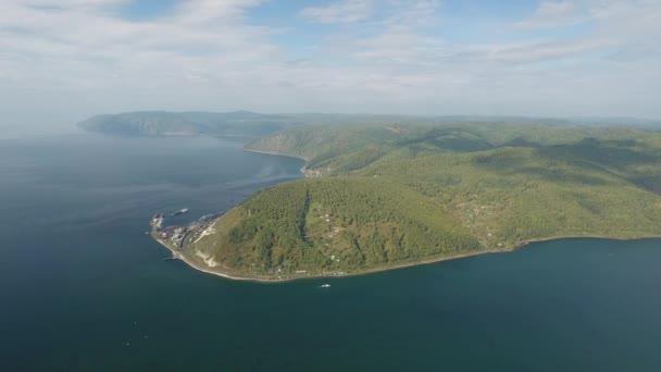 Lake Baikal port. Angara river Russia Siberia. Mountains pine forest. White clouds. Summer sun shines blue water.