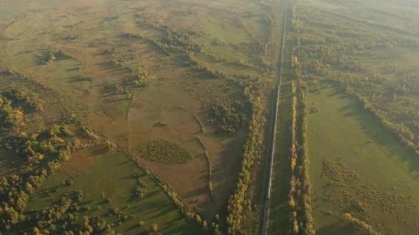 High altitude long passengers train fast ride railway field valley steppe. East Russia Buryatia near Mongolian border. Colorful autumn forest.