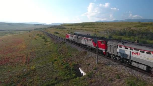 Locomotive train fast ride railway field valley steppe. East Russia Buryatia near Mongolian border. Rails horizon space. Colorful autumn grass.