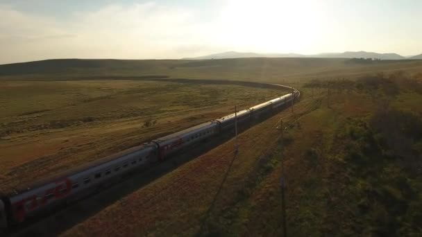 Sunset Long passengers train fast ride field valley steppe turn. East Russia Buryatia near Mongolian border. Rails horizon space.
