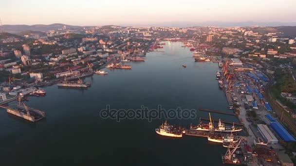 Aranyszarv öböl. A hajó van a vízparti Vlagyivosztok Oroszország kereskedelmi kikötő hajógyárban. Szovjet és modern házak a város ranorama. Tavaszi-nyári meleg fény naplemente.