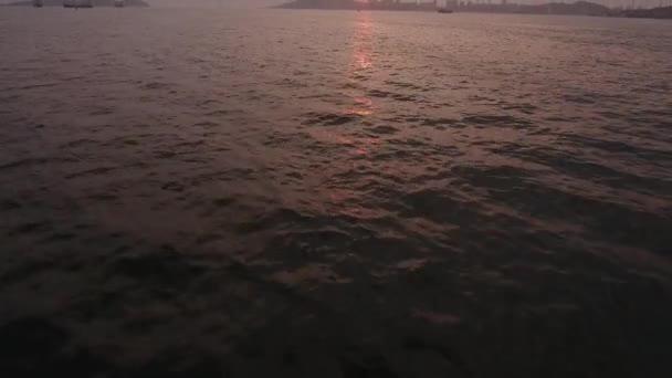 Cinematic forward flight above flat sea waves water camera tilts to horizon with round red sun. Vladivostok Russia city skyline panorama.