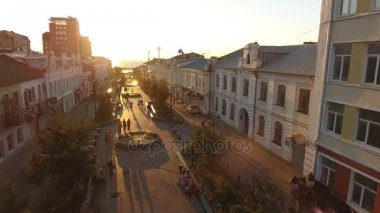 Old small brick houses walking street. Vladivostok Russia Millionka district. Beautiful summer evening sunset. Long shadows. Rooftops mansards. People walk pedestrian