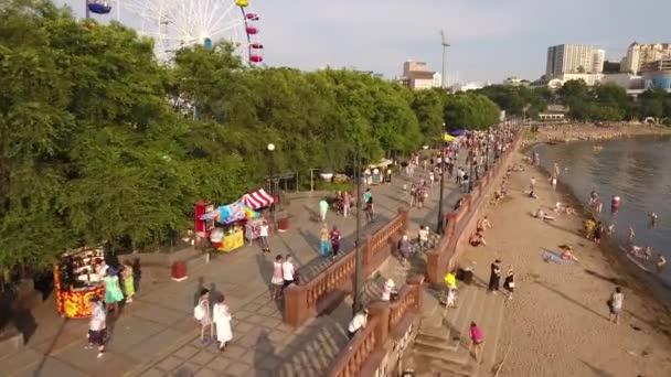 Sportivnaya nábřeží lidé chodí ulici u moře. Vladivostok Rusko. Odraz západu slunce v oceánu. Teplý slunečný den. Centrum pláže města.