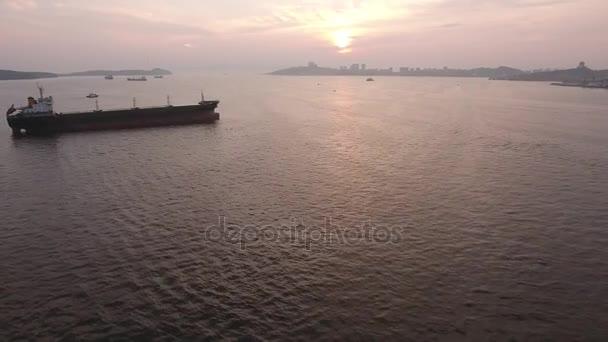 Fishing old trawler industrial ships in port of Vladivostok Primorsky Krai Russia Eastern Bosphorus. City panorama horizon Sea ocean. Orange  pink summer sunset.