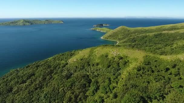Vitiaz blue bay Gamova peninsula. Beautiful Russian nature. Summer sunny day. Forward flight above hill to sea ocean wide panorama.