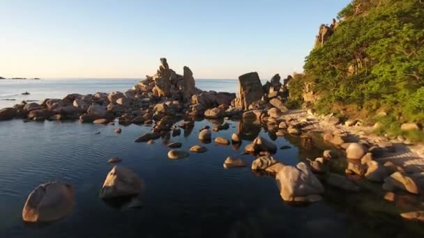 Yellow summer sunrise. Sea water Kekura standing rock stones reflection in the ocean. Unique Far East of Russia natural monument