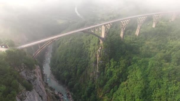 orning fog clouds. Tara river canyon. Best of Montenegro beautiful nature Europe sightseeings. Flight above Concrete arch bridge.