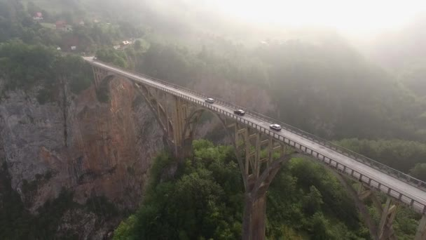 Morning fog. Tara river canyon. Best of Montenegro beautiful nature Europe sightseeings. Follow three cars on concrete arch bridge.