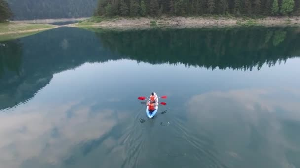 Kayak in Black glacial Lake northern Montenegro Mount Durmitor national park people Unesco list. Famous place for hiking. Summer day morning. Dramatic reflection of sky