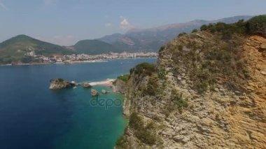 Island of St. Nicholas near Budva. Beautiful Montenegro nature rock mountains city. Beach tourist people rest swim. Cliff rocks above sea.