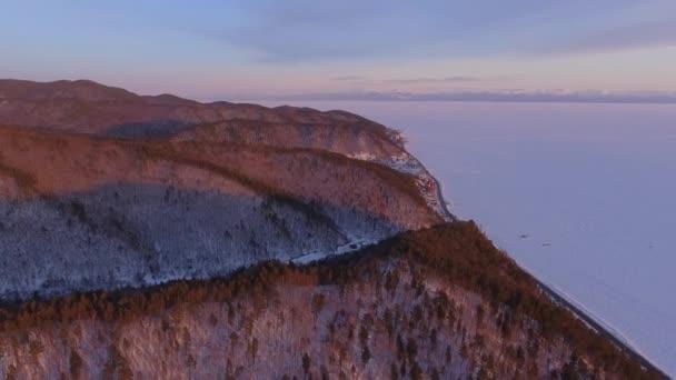 Flight over orange sunset Baikal lake ice. Winter frozen water reservoir. Angara river. Russian forest hills rocks coast.