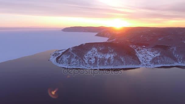 Flight to the sun orange sunset Baikal lake ice. Winter frozen water reservoir. Angara river. Russian forest hills rocks coast.