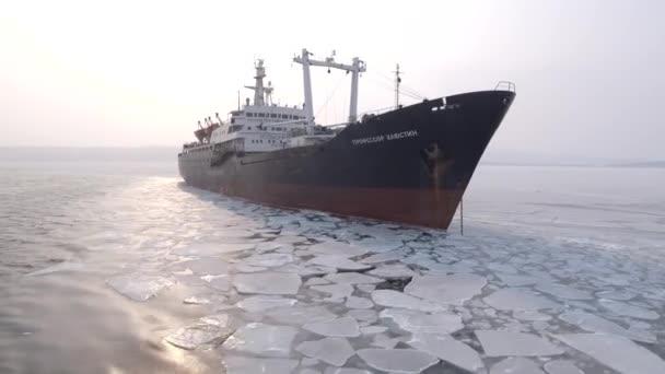 Ruská loď loď v moři oceánu. Zmrazené neobvyklé grafický LED. Hluboké temné modrou vodní pták Racek. ? ity most pozadí. Arktické Severní Rusko. Zimní sněhová sněží zmrazené sunrise. Anténa a okolí. DRONY