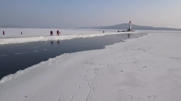 Tokarevsky Lighthouse tower navigační pomoc lamelová odraz ve vodě. Frost zima ledu. Romantický Vladivostok město Rusko vodních moře oceánu rock. Zimní sníh slunce lidé chodí. Letecké letu vpřed