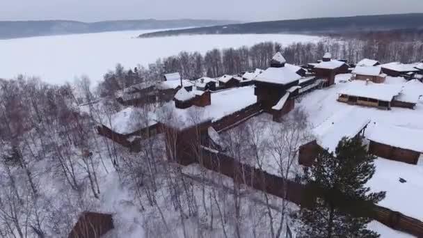 Kinematografická muzeum Taltsy národopisné Open air dřevěné domy, střechy sněhem pole. Historický Rusko Sibiř. Angara řeka pobřežní lesní hory nábřeží. Cestovní ruch. Zimní dramatická obloha. Antény nad