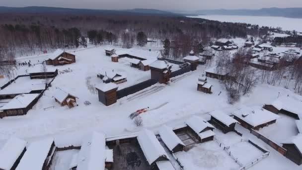 Skvělé vysoké střechy muzea Taltsy sněhu národopisné Open air dřevěné domy historické Rusko Sibiř. Baikalsky traktu. Horské řeky Angary lesní zimní temné Dramatické nebe zataženo. Cestování. Vzdušný Top