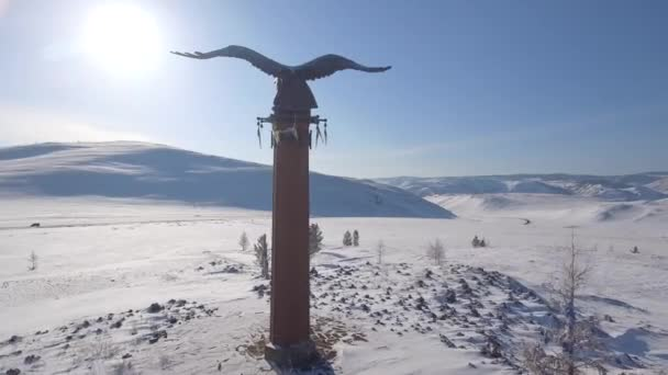 Annäherung Bronzedenkmal stella Adler Schamane buryatia mystisches Ritual einzigartige abgesetzte Flügel hohe Berge offene Raumlandschaft. Winter Schnee Frost kalt blauer Himmel Tag. russland baikal. Drohnen aus der Luft