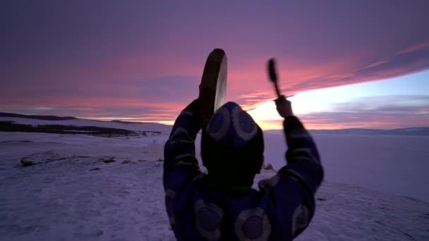 Gimbal Shaman Buryat beats tambourine ritual Close behind Spirit mystical  mysterious appeal  Unique Scenic orange sunset snow field  Costume  authentic reconstruction  Landscape Lake Baikal Russia