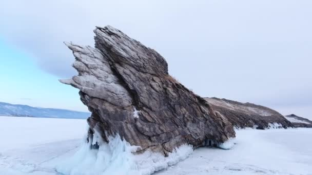 Dramatic graphical gray rock sharp texture white coastal splash ice Ogoy island Baikal lake Russia. Snow field landscape. Winter clouds overcast Visited popular innocent Tourism journey. Aerial Around