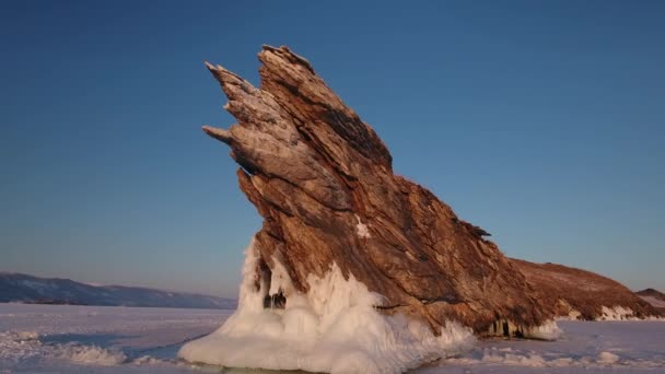 Around Ogoy Island attraction rock beautiful Structure stone Lake Baikal Russia coastal. Untouched innocent majestic. Mountains snow field landscape. Winter orange sunrise. Tourist explore. Aerial