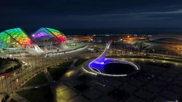 Éjszakai modern olimpiai park sokszínű megvilágítás háttérvilágítás futurisztikus építészet Adler Sochi városkép, egyedülálló Oroszország. Sokan várják az előadást a Stella szökőkútnál. Légi jármű