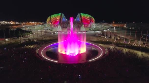 Gyönyörű epikus éneklő szökőkút éjszakai megvilágítás fontos Szocsi Oroszország háttérvilágítás, gyönyörű tánc a víz. A turisták gyülekeznek. Híres üdülőhely rendezvény, olimpiai park falu. Légi jármű
