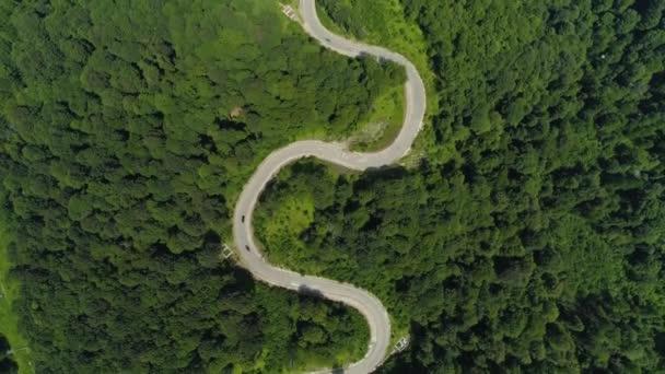 Cinematic vinutí silnice asfalt cesta hadovitá do lyžařského střediska Soči Rusko. Vylez na vrchol hor. Auta. Zelené letní lesní stromy přírodní krajina. Slunečný den. Cestování. Epický let shora dolů