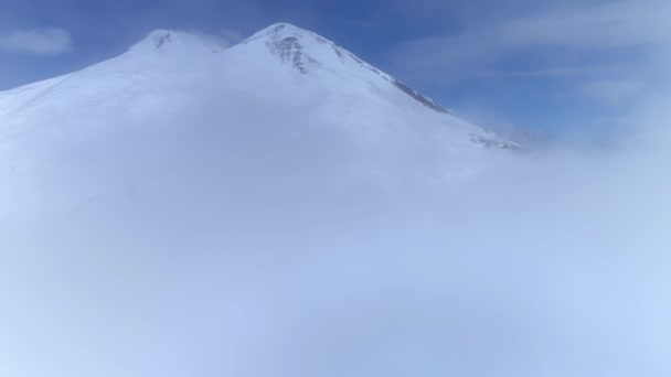 Epic fly out of clouds thick fog to the top Mount Elbrus snowy winter volcanic rocky slopes Circassia highest peak Russia Europe unique natural landscape. Hiking mountaineering Alpine. Aerial