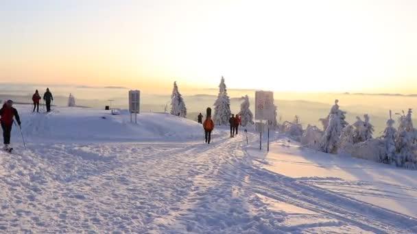 Lysá hora, Beskydy / Česká republika - 8. únor 2020: Muži a ženy se fotí v různých pózách na vrcholu Lysé hory v Beskydech při východu slunce. Země jsou pokryty sněhem. Zmrazené a studené, aby kouzelná země