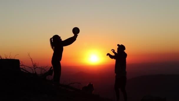 Siluety dvou mladých lidí a jejich psa hrají při západu slunce volejbal na vrcholu hory Ondrejnik v Beskydech. Nikdy nekončící trénink. Potřebuje trénink
